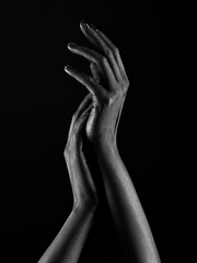Dark-skinned hands over black background. Beautiful hands.