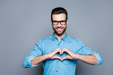 Portrait of happy handsome man in glasses making heart with fing