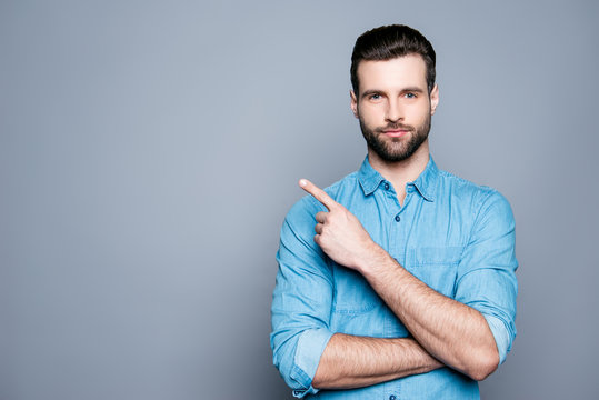 Handsome smiling bearded man pointing away on gray background