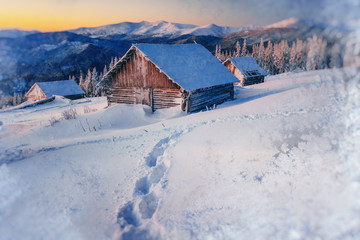 chalets in the mountains at sunset. Winter greetings