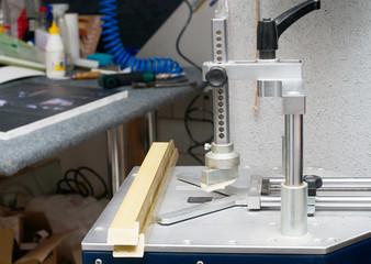 Craftsman working on frame in frame shop. Professional framer hand holding frame angle