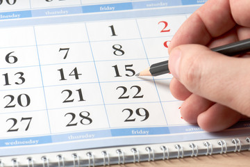 hand with black pencil on calendar