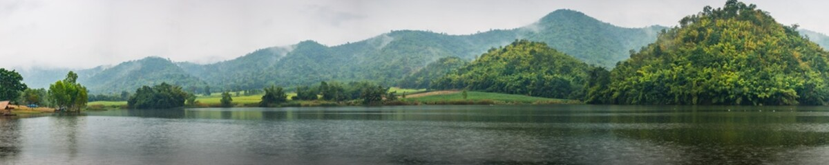 Beautiful tranquil lake and mountain covered with fog. Panorama
