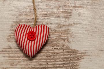Herz aus gestreiftem Stoff hängt vor heller Holzwand