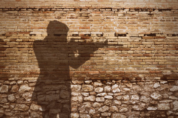 old brick wall with gunman shadow