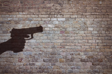 hand holding a gun silhouette on brick wall