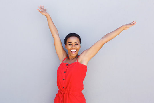 beautiful young black woman smiling with arms raised
