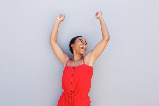 cheerful young black woman with arms raised