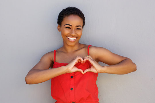 smiling young african american woman with heart shape hand sign