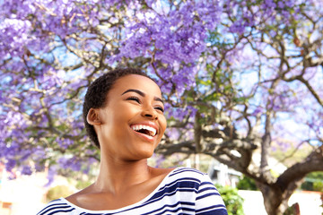 attractive young black woman laughing outdoors by flower tree