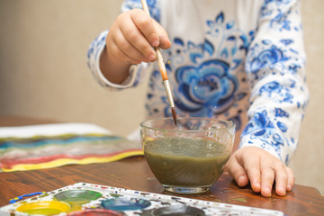 a child draws with watercolors sitting at the table