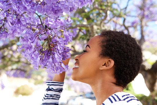 young black woman smelling flowers on tree