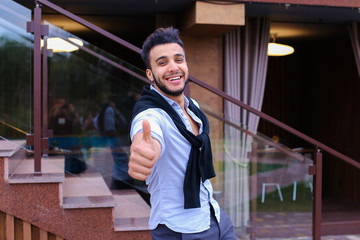 Cheerful young man looks Muslim smiling and showing hand gesture