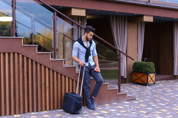 Attractive young Arabic man standing with suitcase in hand and p