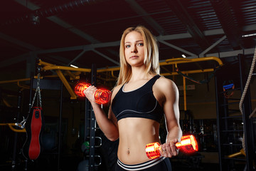 Strong sporty woman bodybuilder with tanned body doing exercises with dumbbell in the gym. Sports and fitness. Fiery dumbbells.