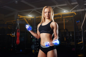 Strong sporty woman bodybuilder with tanned body doing exercises with dumbbell in the gym. Sports and fitness. Neon dumbbells.