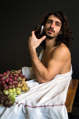 photo half naked handsome guy with long curly hair at the table with a glass of red wine and a plate of grapes in a blissful ecstasy