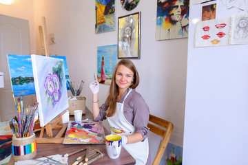 Girl Sits on Stool at Easel And Writing Painting, Uses Brush to