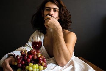 photo half naked handsome guy with long curly hair with a glass of red drink and a plate of grapes at the table
