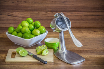 stack of green lemon with aluminum manual juicer squeezer fruit
