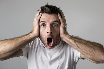 young attractive man astonished amazed in shock surprise face expression and shock emotion