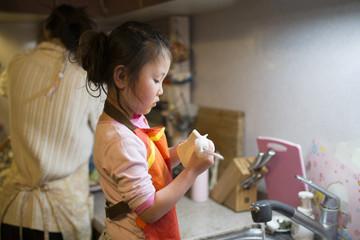 食器洗いを手伝う女の子