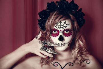 attractive young woman with sugar skull makeup. Mexican Day of the dead woman wearing sugar skull makeup and flower wreath.