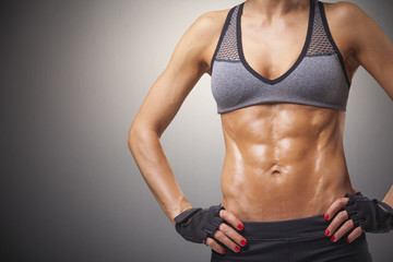Cropped image of a fitness woman on gray background