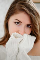 Красивая девушка в свитере позирует в студии