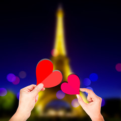 lover hands picking red heart on eiffel tower background at night