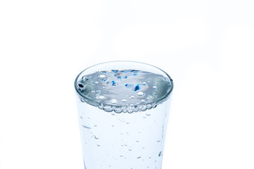 A water glass on white background, isolated in backlight