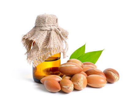 Argan seed  with pharmaceutical bottle. Isolated  on white backg