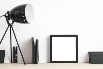 Modern and stylish interior with empty frame, lamp and houseplant. Mock up.