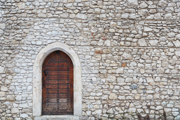 Old wall and the front door in the medieval castle in Krakow