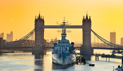 HMS Belfast moored in front of Tower Bridge on the River Thames at sunrise.