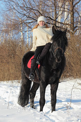 Girl riding horse in winter snow