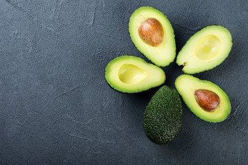 Fresh avocado on dark background. Vegetarian  food concept. Top view.