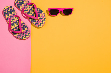 Woman's accessories flat lay on colorful background. Top view. Pink and yellow pastel colors with copy space around products. Horizontal image or photograph.