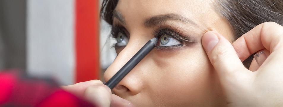 Professional make up artist applies make up on model.