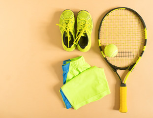 Tennis stuff on cream background. Sport, fitness, tennis, healthy lifestyle, sport stuff. Tennis racket, lime trainers, tennis balls, lime athletic shorts. Flat lay, top view.