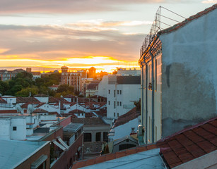 Dramatic color sunset rooftops of Madrid.  Glowing fiery orange Madrid sky & rooftops at sunset.   elevated view of urban homes and apartment buildings in the city at evening.