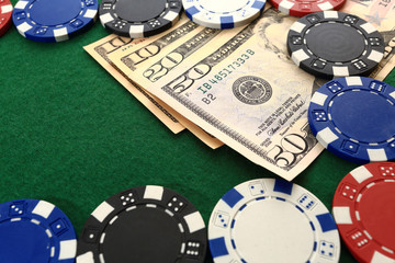 Dollars and chips on green casino table closeup