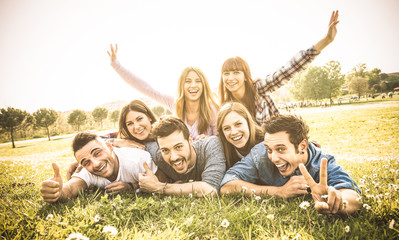 Friends group having fun together with self portrait on grass meadow - Friendship youth concept with young happy people at picnic camping outdoor - Warm vintage filter with backlight contrast sunshine