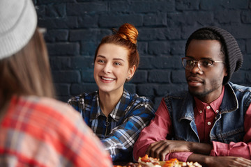 Stylish young interracial couple having lunch at restaurant. Redhead woman with hair knot and African male in trendy black hat and glasses sitting at table with food and talking to unrecognizable girl