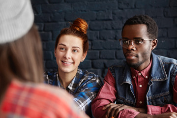 Beautiful young Caucasian woman with cheerful smile and African male hipster wearing spectacles relaxing at coffee shop at weekend, having lively conversation with their common female friend