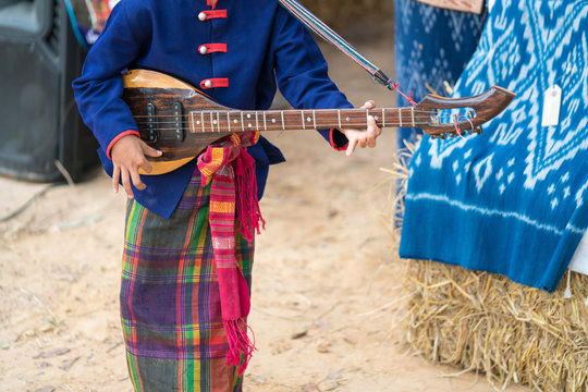 Thai Musician, A Boy playing northeastern Thailand music instrument lute. Studen artist playing Phin stringed plucked instrument Thai culture