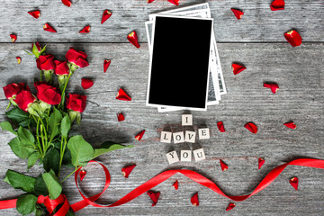i love you inscription with blank photo frame and red roses