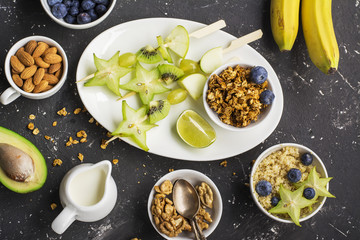 Ingredients for a healthy breakfast,avocado, quinoa bowl, carambola, green apple, banana, kiwi, nuts, oatmeal, berries fruits blueberry almonds walnuts Top view. Greenery