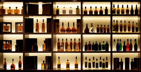 Various alcohol bottles in a bar, back light, logos removed