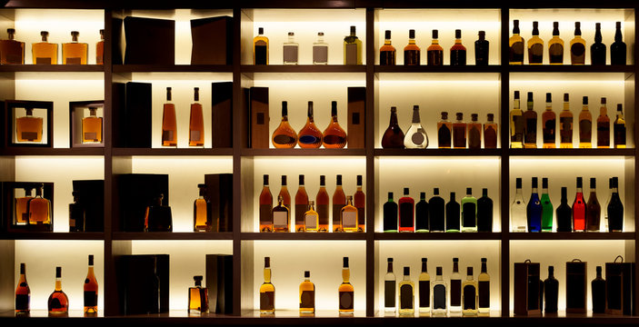 Various alcohol bottles in a bar, back light, logos removed
